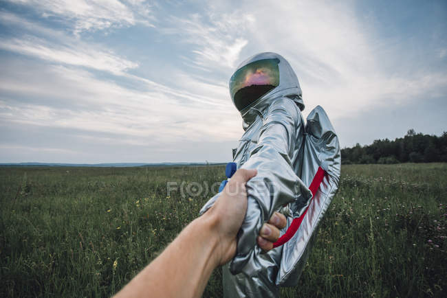 Spaceman exploring nature, holding hands with human — Stock Photo