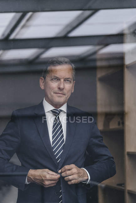 Businessman looking out of window while buttoning jacket in office — Photo de stock