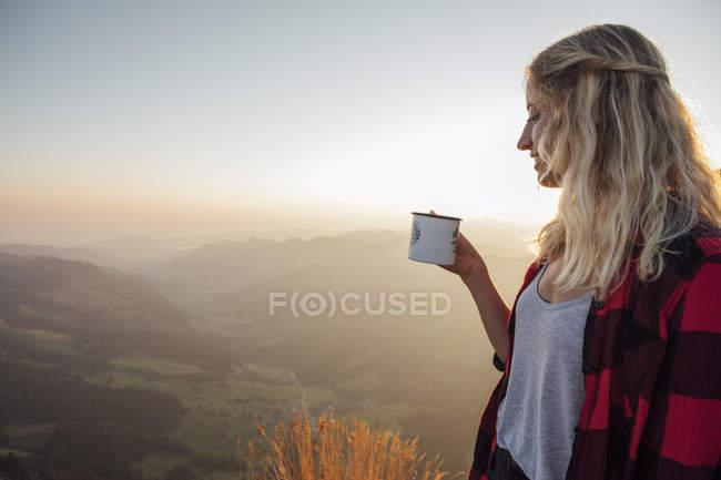 Швейцария, Гроссер Митен, молодая женщина в походе на рассвете держит чашку — стоковое фото