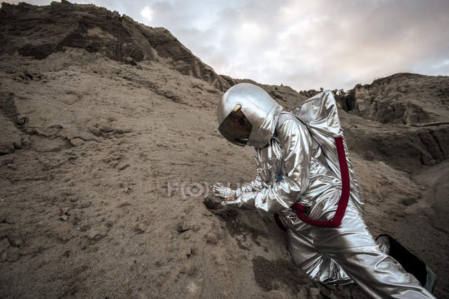 Spaceman on nameless planet, taking rock samples — Stock Photo