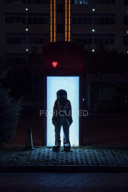 Raumfahrer steht nachts an beleuchteter Box — Stockfoto