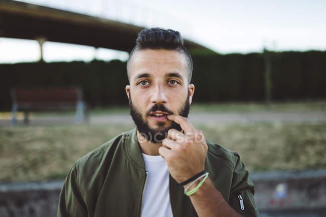 Портрет молодого чоловіка з пальцем на роті. — стокове фото