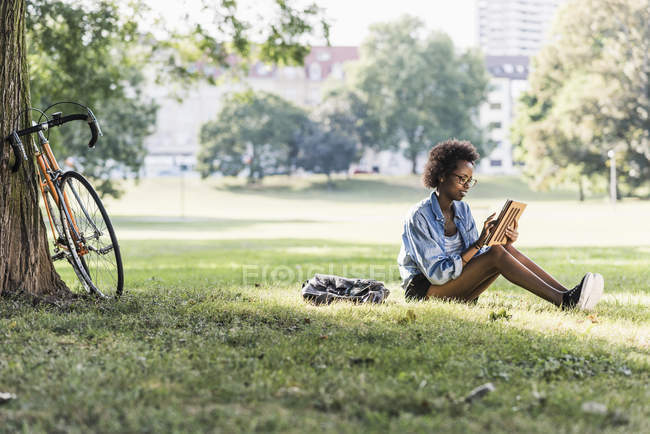 Young woman resting in park using tablet — Stock Photo