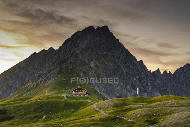 Germany, Bavaria, Allgaeu, Allgaeu Alps, Fiderepass hut and Hammerspitze in the evening — Fotografia de Stock