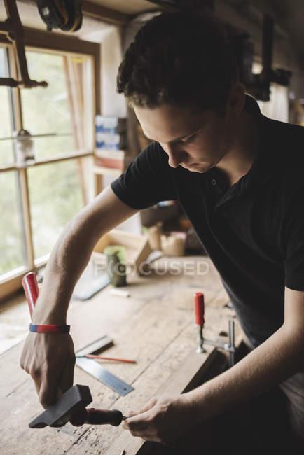 Tischler bearbeitet Stück Holz in Werkstatt — Stockfoto