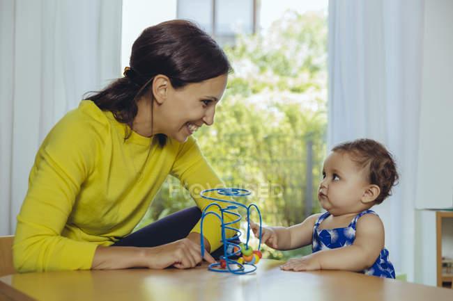 Feliz madre y bebé hija jugando con bucle motorizado - foto de stock