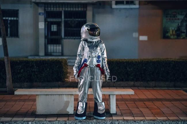 Spaceman de pie en el banco en la ciudad por la noche - foto de stock