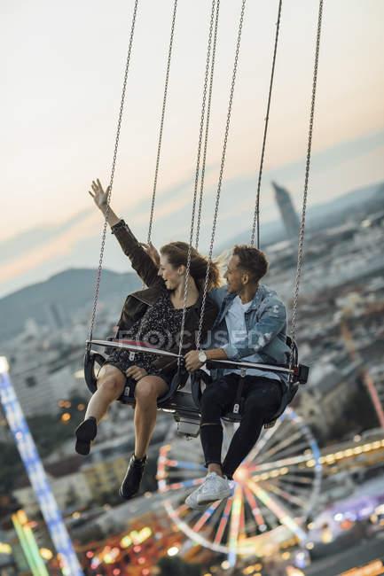 Jovem casal apaixonado, andar de chairoplane em um recinto de feiras — Fotografia de Stock