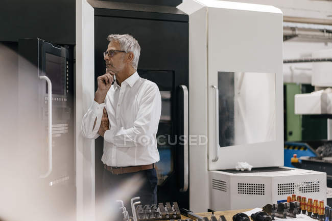 Manager in high-tech company thinking with hand on chin — Stock Photo