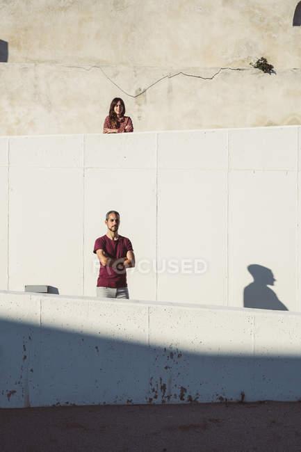 Mann und Frau stehen auf verschiedenen Ebenen einer Mauer, die Arme verschränkt — Stockfoto