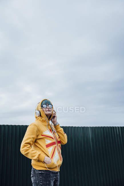 Портрет молодой женщины с голубыми волосами и наушниками в модной куртке в капюшоне — стоковое фото