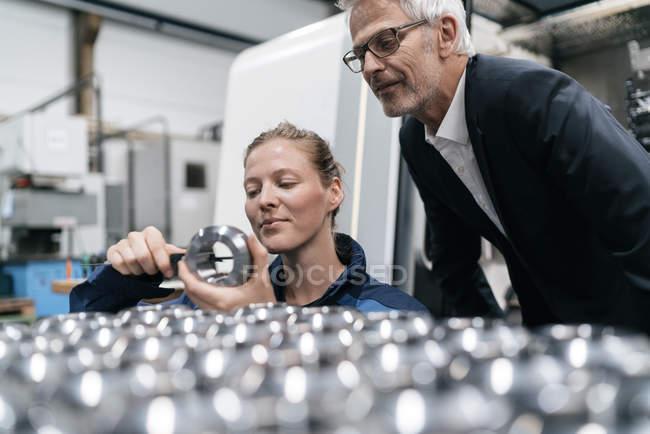 Gerente e trabalhador hábil na empresa High-Tech, verific as peças da máquina — Fotografia de Stock
