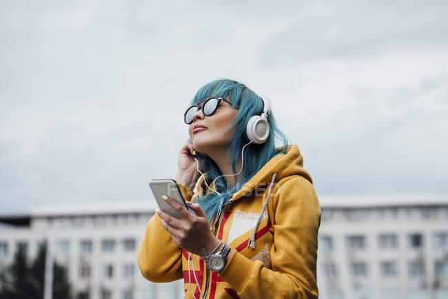 Портрет молодої жінки з фарбованим синім волоссям прослуховування музики з смартфоном і навушниками — стокове фото