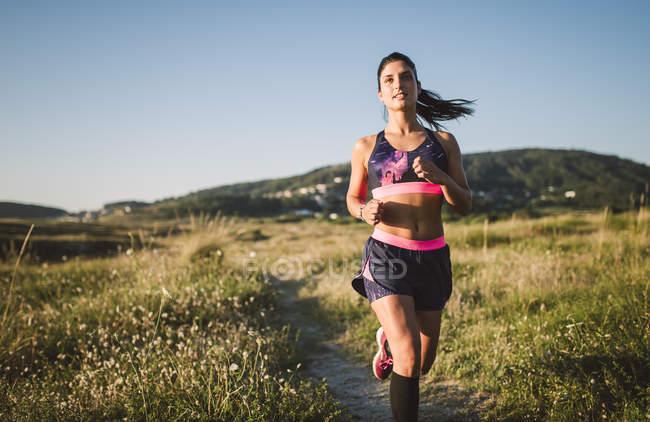 Attrayant sportif jogging sur le chemin dans la nature — Photo de stock