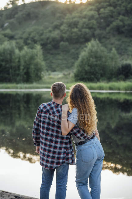 Romantic couple standing at riverside and embracing — Stock Photo