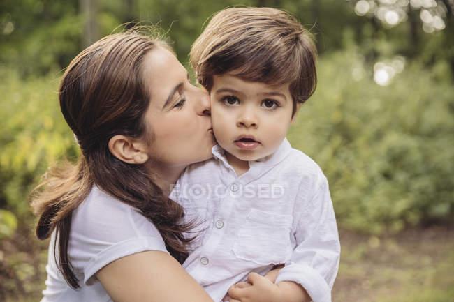 Madre besando niño en la mejilla en el parque - foto de stock