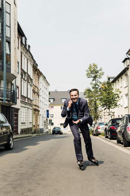 Empresário no celular patinação em linha na cidade — Fotografia de Stock