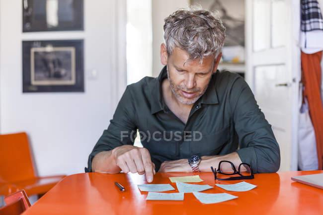 Maduro homem sentado à mesa em casa olhando para notepads — Fotografia de Stock