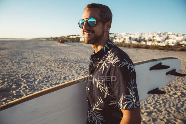 Homem na praia carregando prancha — Fotografia de Stock