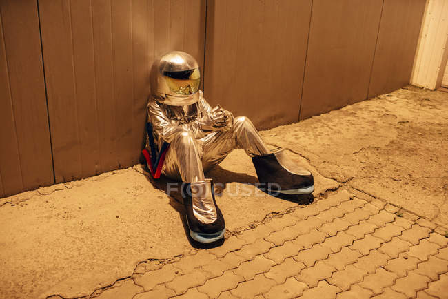 Spaceman sitting at metal wall at night — Stock Photo