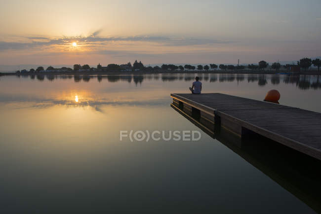 Relaxed girl on the floating platform on the lake at sunrise — Stock Photo