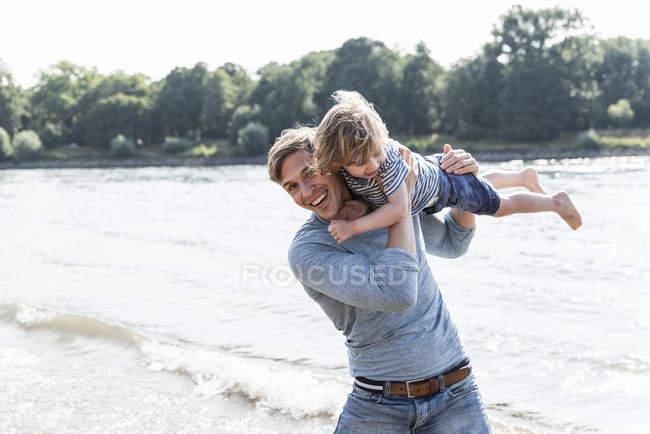 Père et fils ayant l'amusement au bord de la rivière — Photo de stock