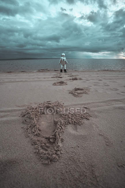 Lonely spaceman looking at lake on nameless planet — Stock Photo
