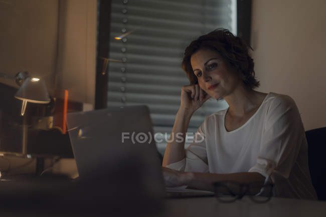 Businesswoman working overtime, using laptop — Stock Photo