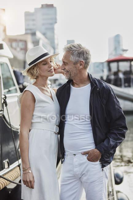 Мужчина и молодая женщина с разницей в возрасте флирт рядом с яхтой — стоковое фото