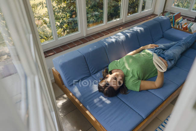 Mature woman lying on couch at home reading book — Stock Photo