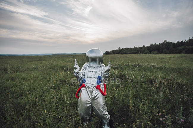 Spaceman fooling around in green meadow — Stock Photo