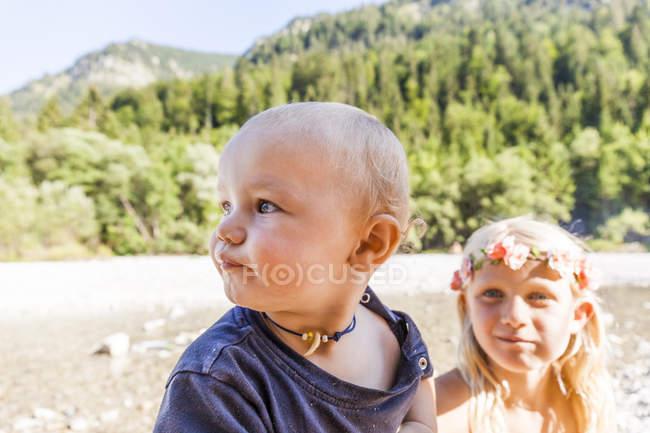 Портрет хлопчика і дівчинки у квітковій короні на вулиці влітку. — стокове фото