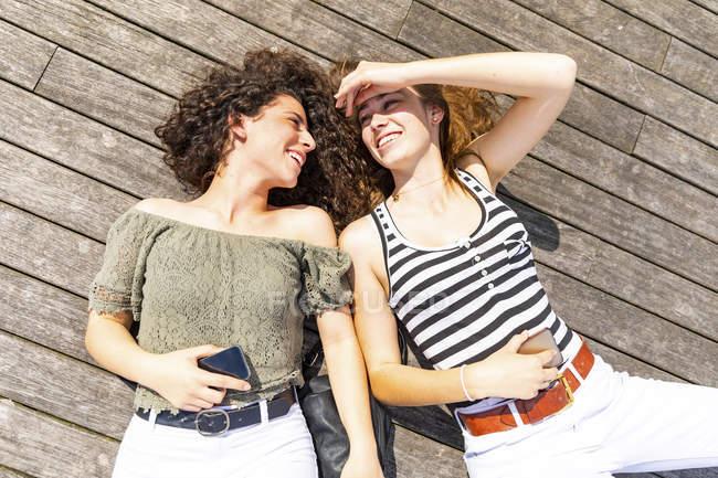 Две счастливые подружки лежат на деревянном полу — стоковое фото