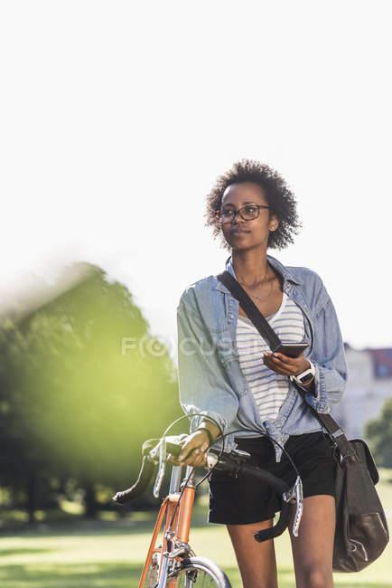 Молодая женщина с сотовым телефоном толкает велосипед в парке — стоковое фото