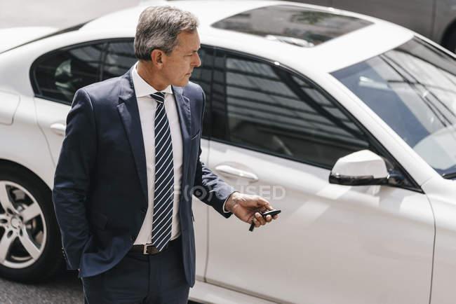 Businessman using remote control key of car — стокове фото
