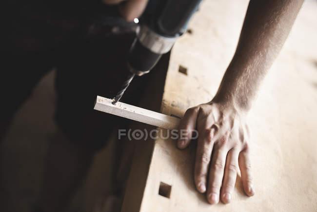 Nahaufnahme des Zimmermanns mit Bohrer auf Holzstück in der Werkstatt — Stockfoto