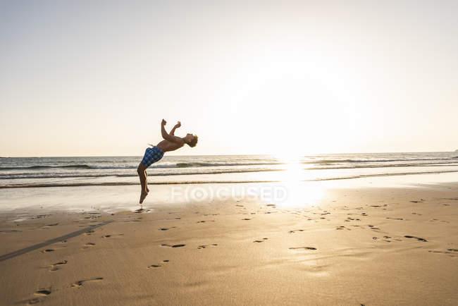Молодой человек делает сальто на пляже на закате — стоковое фото