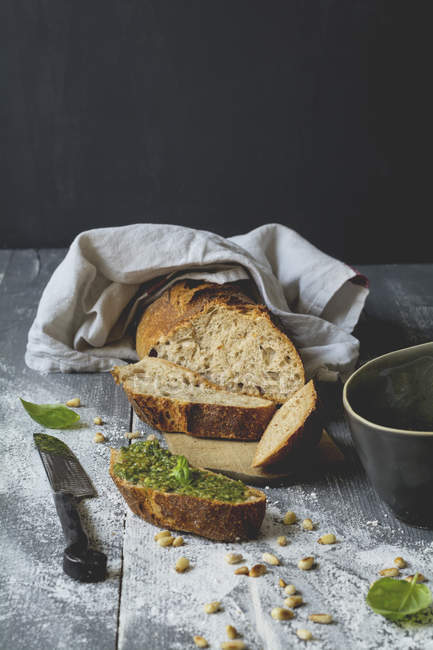 Homemade basil pesto, rye baguette on wood — Stock Photo