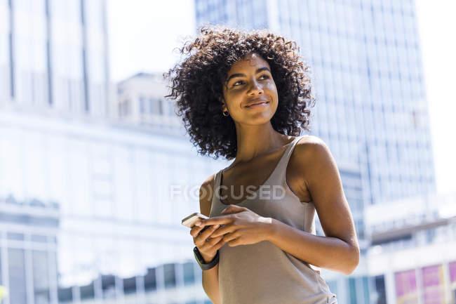 Улыбающаяся молодая женщина с вьющимися волосами с помощью мобильного телефона перед небоскребами — стоковое фото
