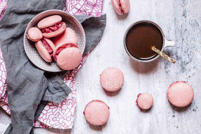 Pink macarons filled with raspberry buttercream and a cup of coffee — Stock Photo