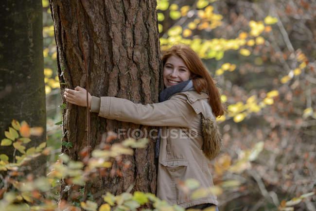 Retrato de menina adolescente feliz abraçando tronco de árvore na floresta outonal — Fotografia de Stock