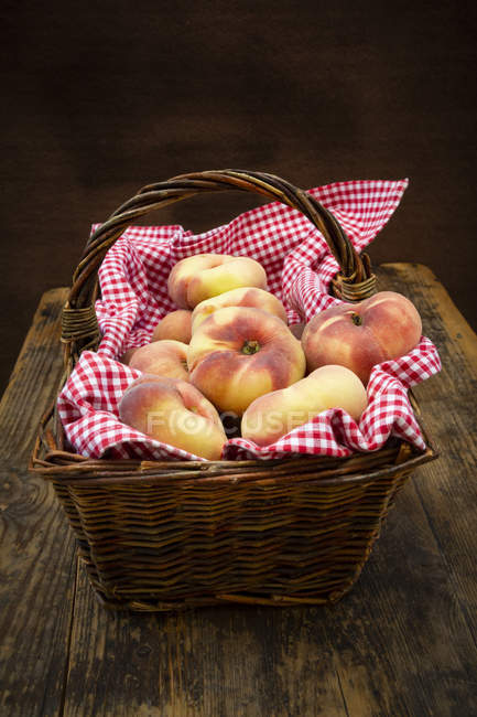 Doughnut peaches in wickerbasket — Stock Photo
