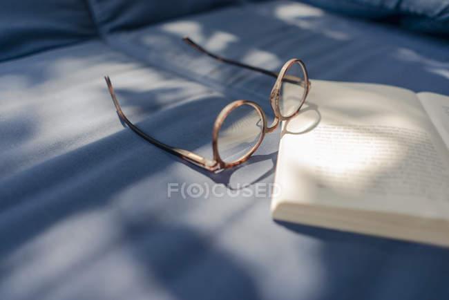 Lunettes de vue et livre couché sur le canapé — Photo de stock