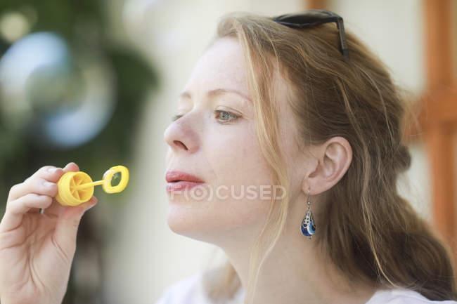 Молодая женщина надувает мыльный пузырь — стоковое фото