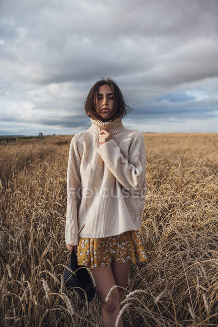 Portrait of young woman wearing oversized turtleneck pullover posing in corn field — Photo de stock