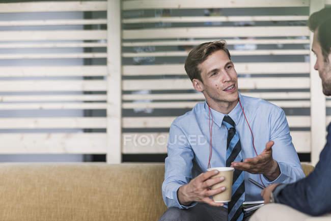 Homme d'affaires parlant à un collègue dans le salon de bureau — Photo de stock
