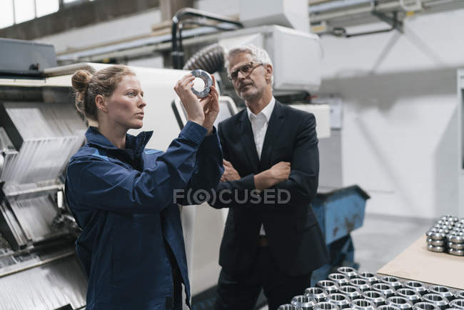 Manager and skilled worker in high-tech enterprise, checking machine parts — Stock Photo