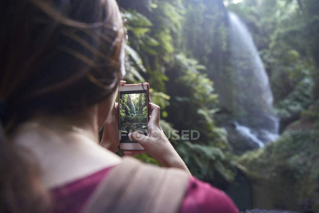 Woman taking photo of a waterfall in a forest — Stock Photo