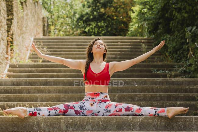 Молодая женщина практикует пилатес на лестнице в городском парке — стоковое фото