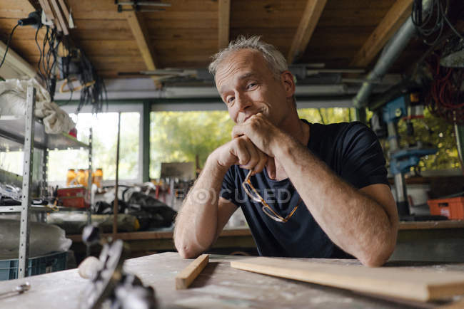 Portrait of confident mature man at workbench in workshop — Stock Photo